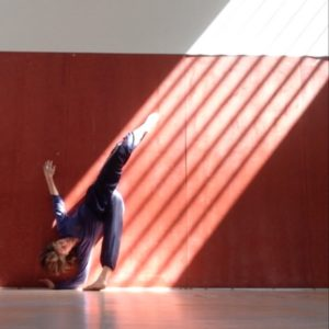 Still shot of dance teacher with one leg in air